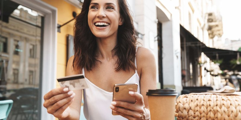 A woman smiles as she types her credit card details into her phone while sitting on a patio