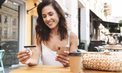 A woman looks at her credit card while holding her smartphone