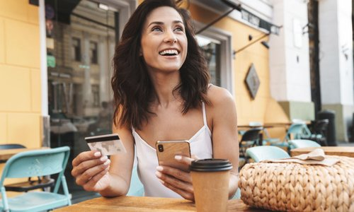 A woman looks up and smiles while holding her credit card and smartphone