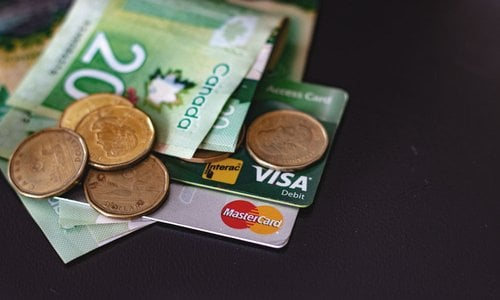 A pile of credit cards, Canadian banknotes and coins