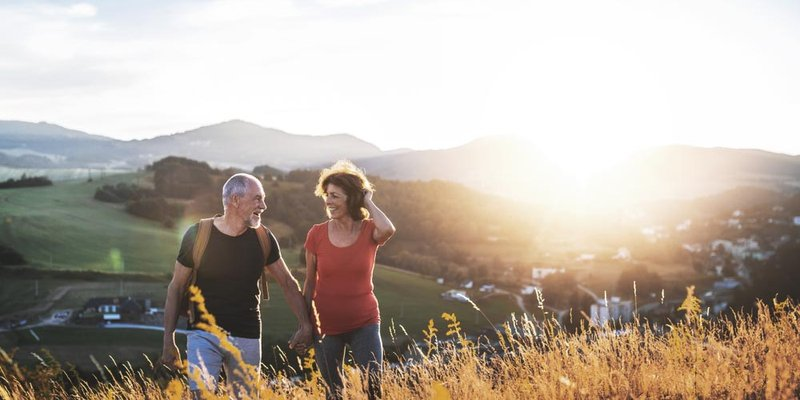 A older woman and man walk up a hill as the sun sets behind them