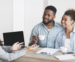 A couple sits with coffee mugs and speaks with a mortgage broker or financial advisor