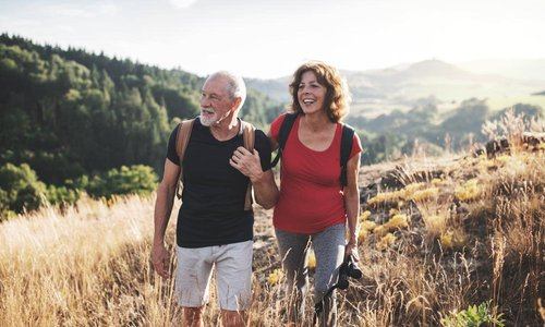 An older man and woman carry backpacks and walk outdoors