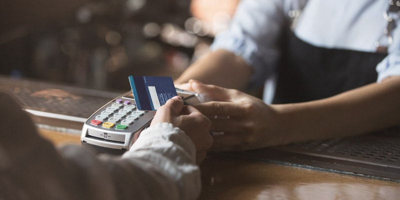 A person taps their credit card on a point of sale terminal
