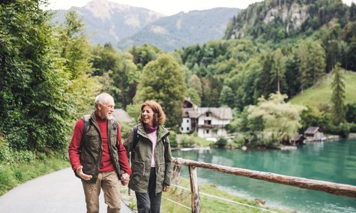 An older couple walk around a scenic lake