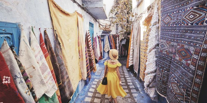 A woman in a flowing yellow dress walks down a marketplace with rugs hanging
