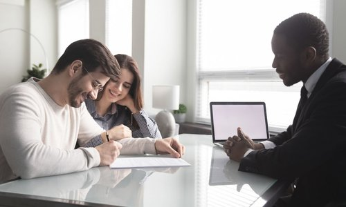 A realtor helps a young couple with paperwork