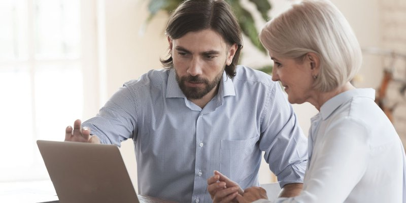 A younger man shows an older woman something on a laptop