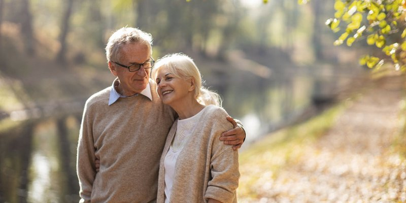 A senior couple embrace as they walk along the river