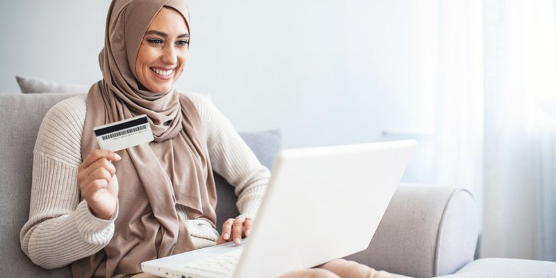 A woman sits on her couch and online shops using her credit card