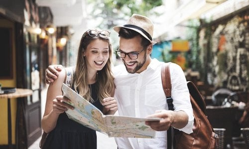 A young couple laugh as they read a map and find their directions