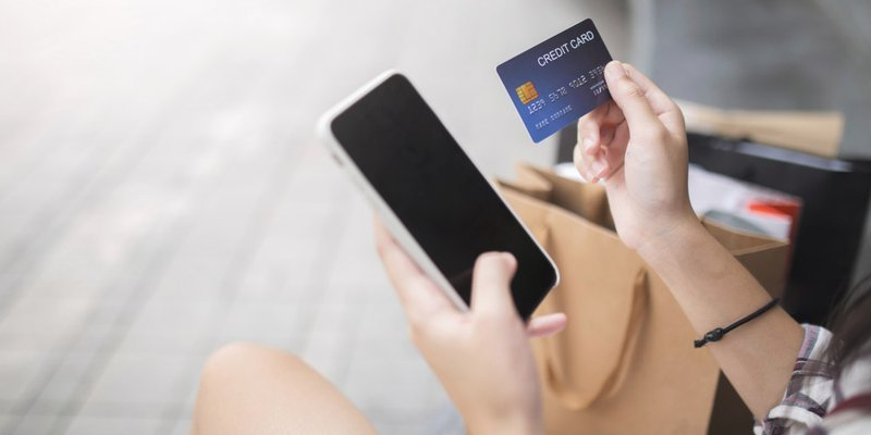 A person types their credit card information into their smartphone with shopping bags rested alongside them