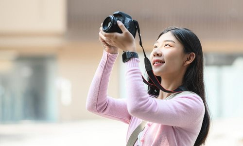 A young woman holds up her camera to take a picture