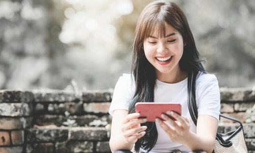 A young woman laughs as she holds her phone while sitting on steps