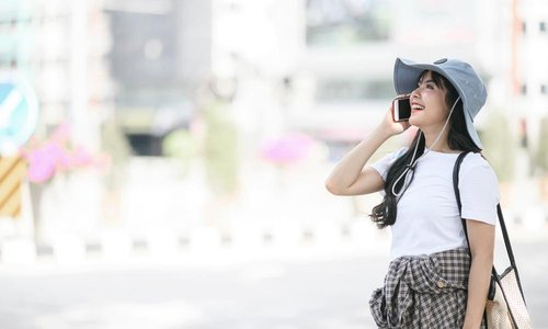 A young woman wearing a big floppy hat talks on the phone