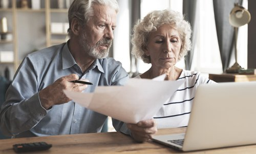 A senior couple review their finances with a laptop and paperwork