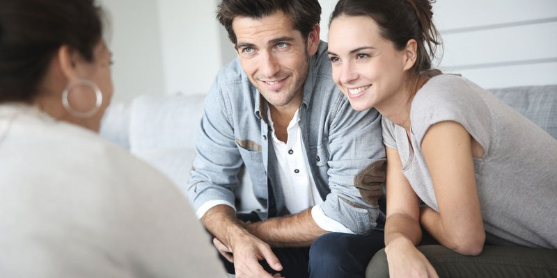 A smiling young couple speak with a designer about paint colours