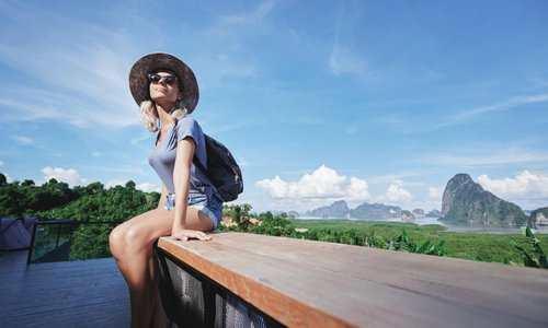 A woman wearing a sun hat sits on a railing with a mountain view