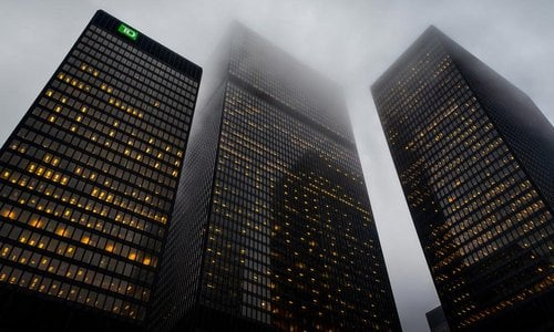 A fog settles around the top of large buildings in the financial district in Toronto