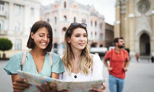 Two woman hold a map and look for directions