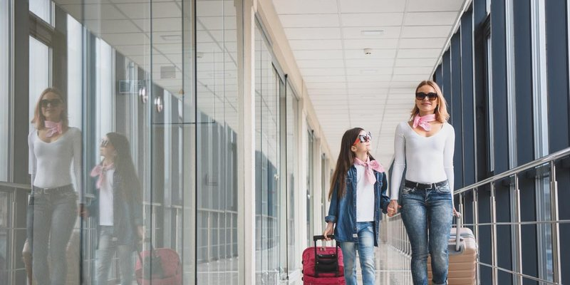 A mother and daughter wheel their suitcases in the airport