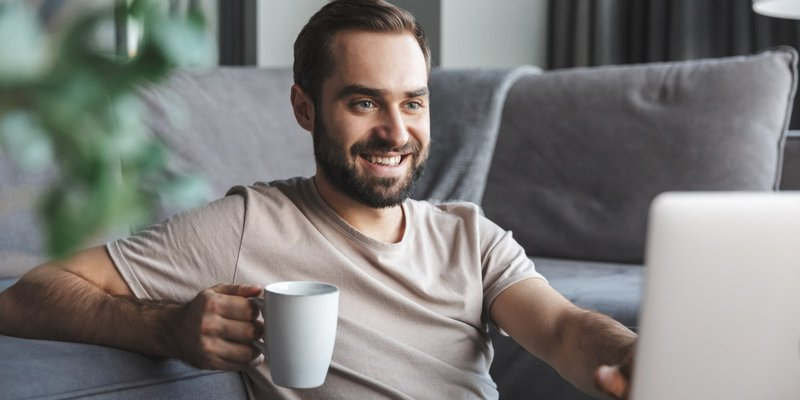 A man smiles and types on his computer with a coffee mug in one hand