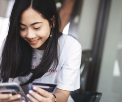 A young woman shops on her smartphone using a credit card