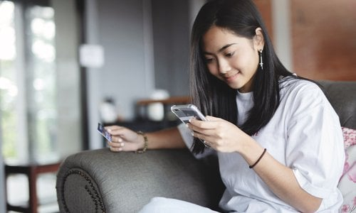 A young woman sits on a couch and shops using her phone and a credit card