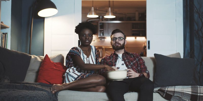 A couple sit on the couch and watch a movie with popcorn