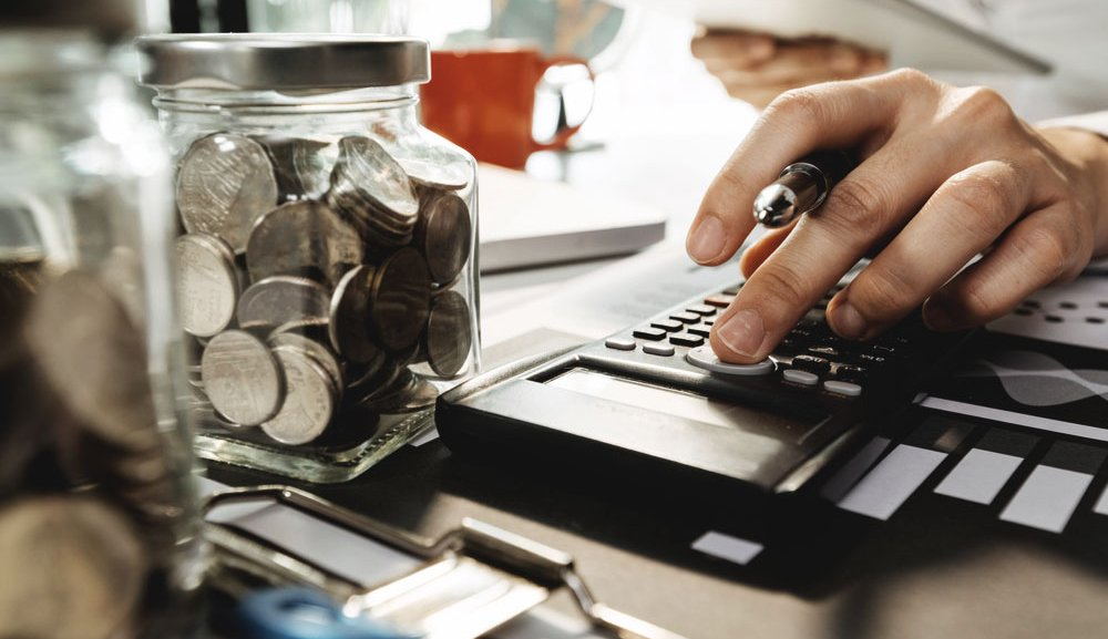 A person uses a calculator while holding a tablet at a desk covered with jars of coins