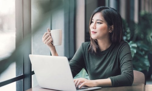 A woman holds up her coffee mug and stares out the window as she works on her laptop