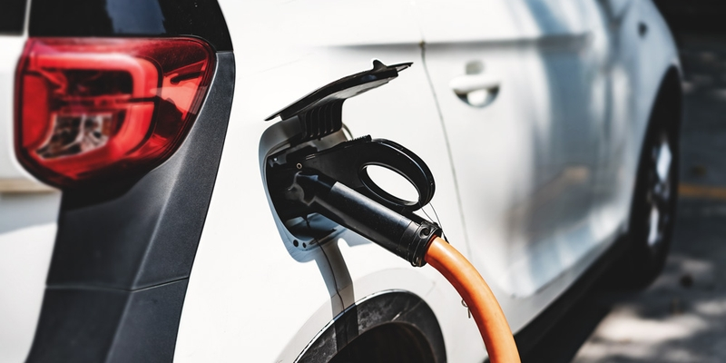 A white electric vehicle charges