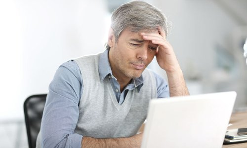 An older man looks frustrated at something on his laptop