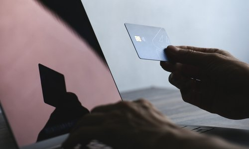 A person uses their credit card and a laptop computer