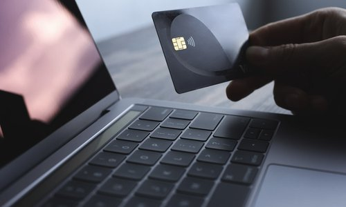A close-up view of a credit card and a laptop computer