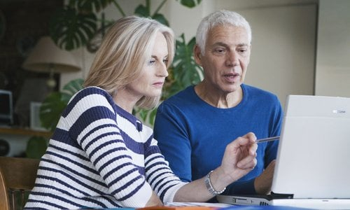 An older woman leans toward an older man and points to something on the laptop screen