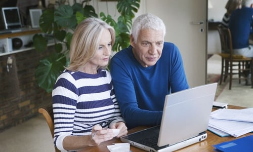 An older couple lean in to look at something on the laptop screen