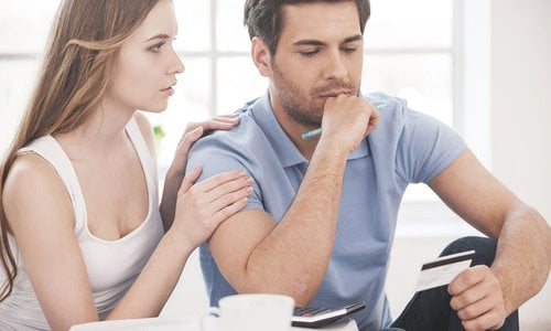 A young woman comforts a man looking worried and holding a credit card