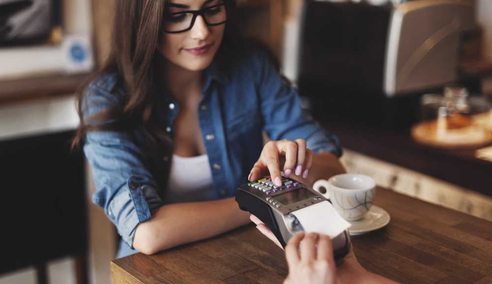 A woman uses the point of sale terminal to pay for her drink at a cafe