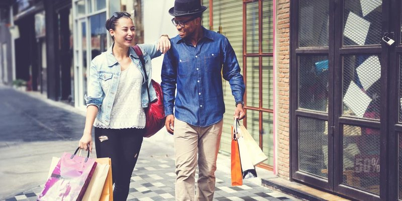 A young couple walk down a sunny street with shopping bags