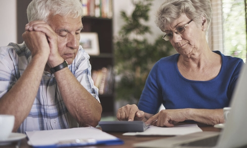 A senior couple look unhappy while reviewing their finances