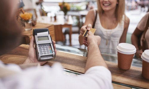 A woman hands her credit card to the cashier to pay for her coffees