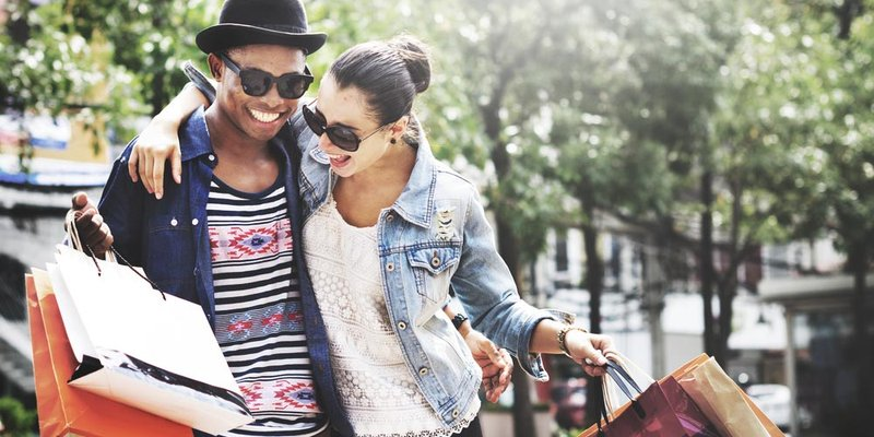 A man and a woman embrace happily as they walk down the street with shopping bags