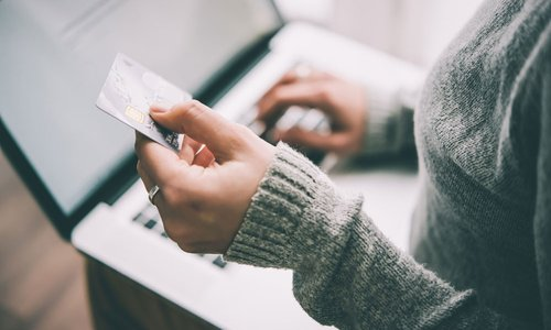 A woman types her credit card details into her computer