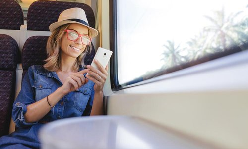 A woman uses her phone while looking out the window of a train