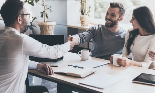A man embraces his partner and shakes the hand of a financial advisor