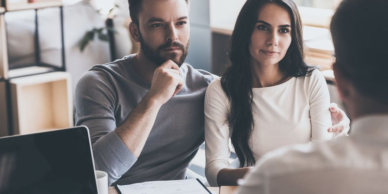 A young couple speak with a broker or advisor