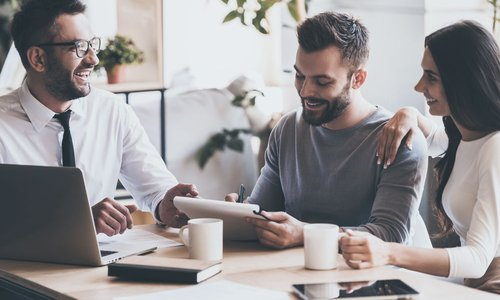 A man and his partner sign mortgage documents