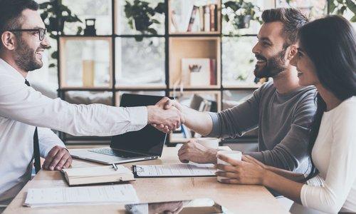 A couple shake hands with a financial advisor