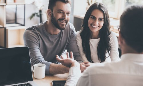 A young couple smiles while listening to a mortgage broker speak
